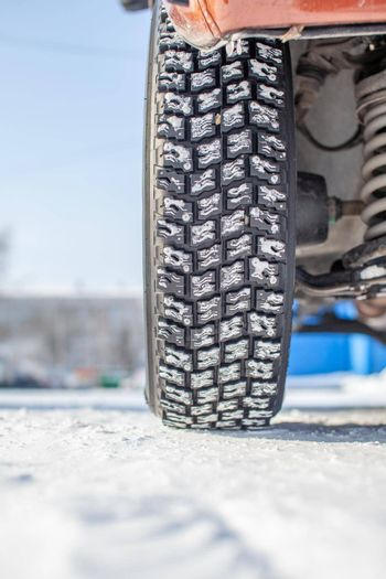 Car wheel on snow in winter close-up. The suspension and chassis of the car are visible. The car is parked in a snowy parking lot.