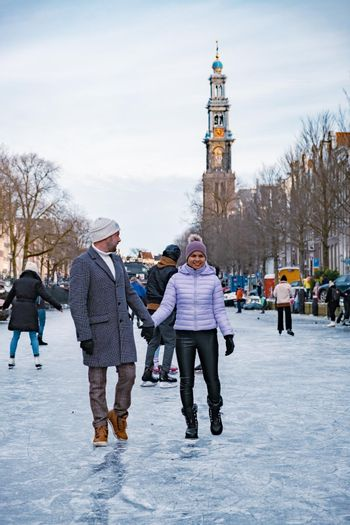 couple visit Amsterdam during Winter with people Ice skating on the canals in Amsterdam the Netherlands in winter, frozen canals in Amsterdam during winter.