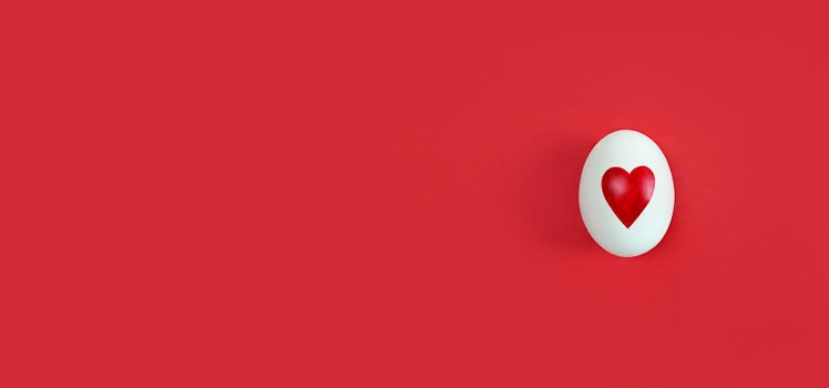 White egg with heart shape on a red background with copy space.