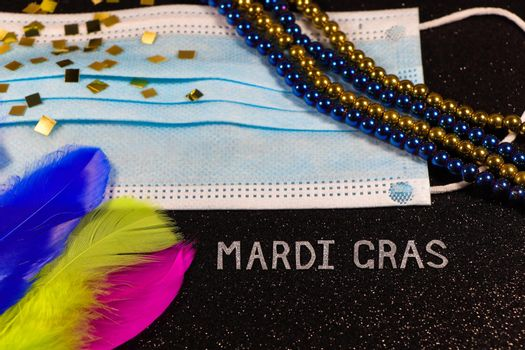 Mardi Gras carnival theme medical facemask with feathers and bead strings abstract on textured black