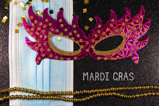 Mardi Gras carnival theme pink party mask with medical facemask and bead string layout on textured black