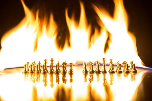 Сhess pieces on the chessboard against the background of a burning fire. Selective focus