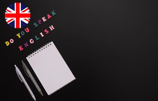 Do You speak English. School for the study of the English language. A blank notebook, a pen, the flag of the United Kingdom on a black background. Mock up