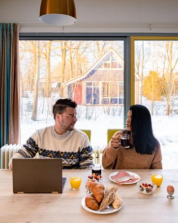 Young couple morning breakfast with laptop.Love,happiness,people and fun working from home concept. young couple mid age Asian and Causian man and woman working from home with laptop