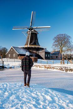 Pelmolen Ter Horst, Rijssen covered in a snowy landscape Overijssel Netherlands, historical wind mill during winter. wooden old windmill in Holland, couple men walking in the snow