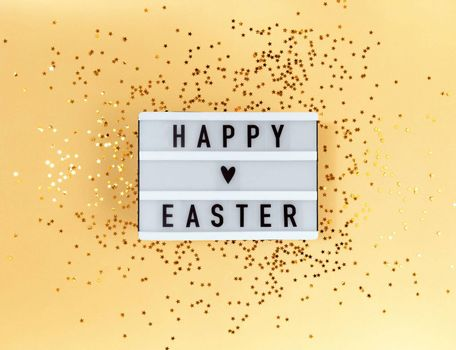 Happy Easter greeting on light box and confetti on a yellow background.