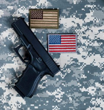 Military pistol and US flags for the holidays of Memorial, 4th of July and Veterans Day