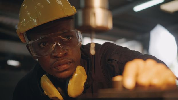 worker man with yellow helmet and ear protection manual rotating on drill machine