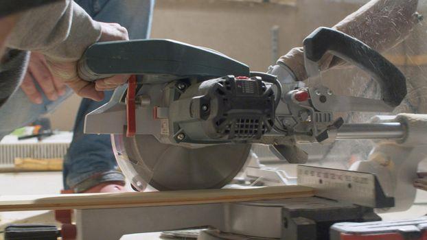 Carpenter cutting a plank with circular saw