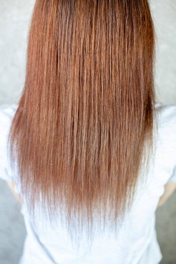 A girl with long, straight and beautiful brown hair. Hair care at home.