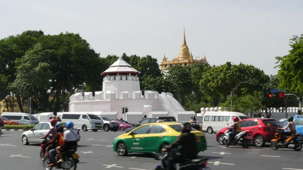 BANGKOK, THAILAND - 11 JULY, 2019: Rush hour traffic near Wat Saket in capital. Famous asian landmark and travel destination. Ancient religious monastery and public transport on the road in downtown.