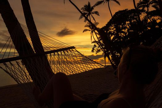 young women enyoing view of a colorful sunrise on the Tambua Sands Beach on Fiji Island in a hammock, Fiji