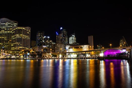 Night City Skyline of Darling Harbour, Australia, with light reflection on calm water