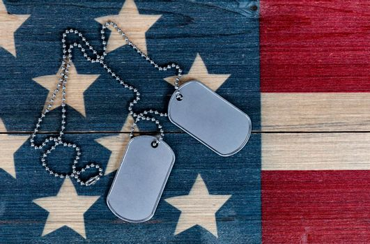 Close up view of military ID tags for Memorial, 4th of July and Veterans Day holiday on rustic US wooden flag background