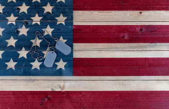 Military ID tags for Memorial, 4th of July and Veterans Day holiday on rustic US wooden flag