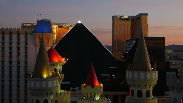 LAS VEGAS, NEVADA USA - 4 MAR 2020: Excalibur castle and Luxor pyramid casino uncommon aerial view. Plane flying from McCarran airport. Mandalay Bay and Delano hotel in american gambling sin city