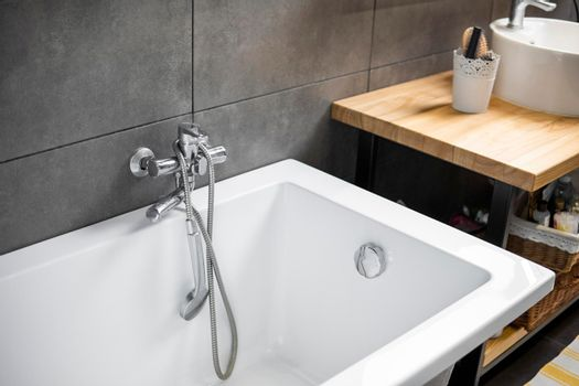 Bathroom interior with grey tile on a wall, stylish white bath with a silver tap. Minimalism in interior of bathroom.