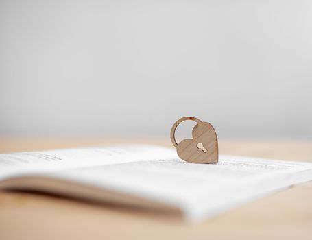 A wooden heart with a keyhole rests on an open book. There is a place for the text.