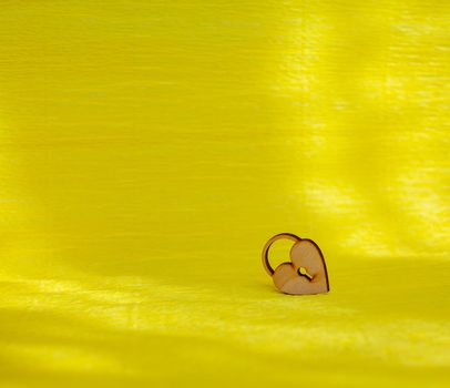 A wooden heart with a keyhole on a yellow background. There is a place for the text.