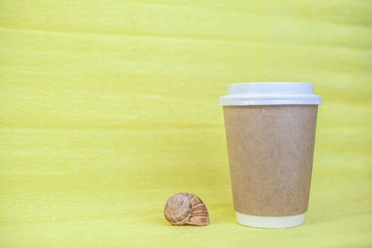 A paper cup of coffee covered with a white lid and next to it sea shells on a yellow background. There is a place for the text.