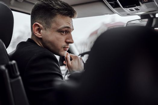 Confident businessman is sitting in modern automobile