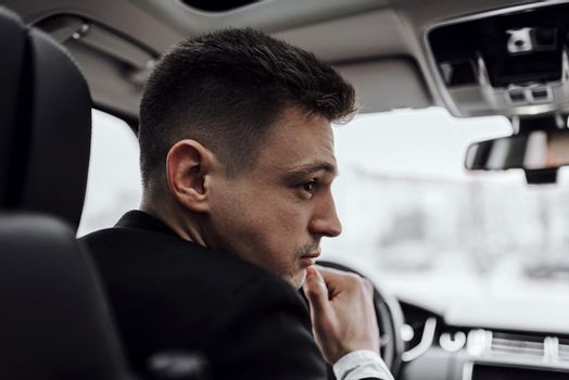 Handsome businessman is resting in modern automobile