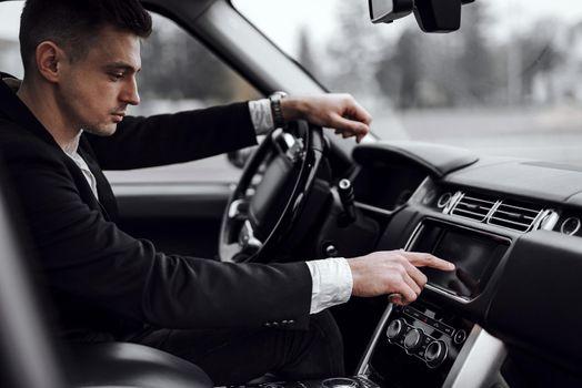 Businessman in jacket sitting in modern automobile