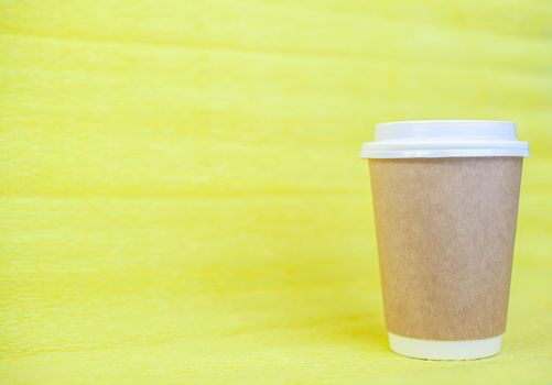 Paper cup of coffee closed with a white lid on a yellow background. There is a place for the text.