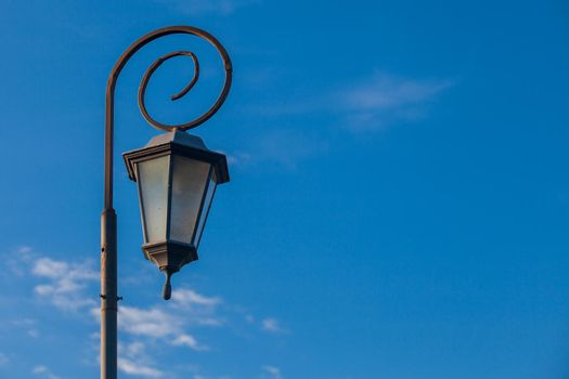 Antique style lampposts against a bright blue sky
