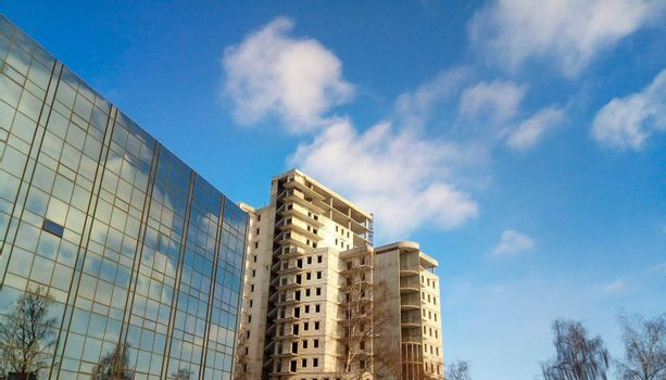 A new city building, a gray, multi-story building next to a glass facade. Blue sky and clouds are reflected in the glass.