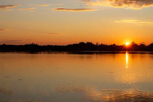 Colorful sunny sunset on a calm lake. The sun is reflected on the surface of the water.