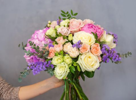 Close up view of a beautiful bouquet of mixed coloful flowers in a florist hand. The concept of a flower shop and flower delivery as a family business, florist work.