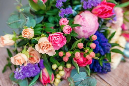 Close up view of a beautiful bouquet of mixed coloful flowers on wooden table. The concept of a flower shop and flower delivery as a family business, florist work.
