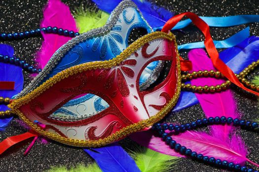 Mardi Gras carnival theme parade face masks with vibrant feathers and bead strings on textured black