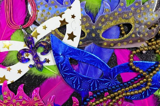 Mardi Gras carnival theme parade flat face masks with feathers and jewelry layout on textured black