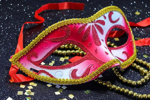 Mardi Gras red carnival face mask with gold bead string and confetti on textured black