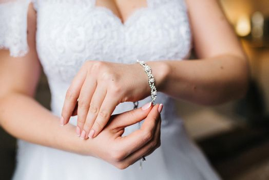the bride wears a bracelet with transparent stones on her hand