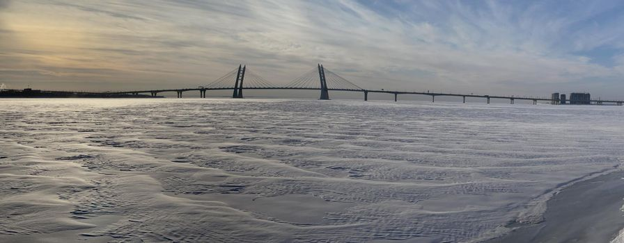 Winter panorama of the Guy three-flying pilonny bridge through the Ship waterway at sunset, Russia, Saint Petersburg, The frozen river Neva,