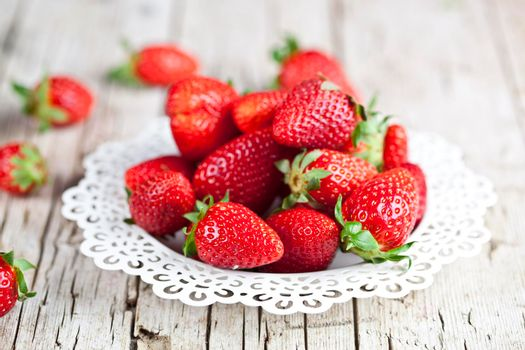Fresh red strawberries on white plate on rustic wooden background. Healthy sweet food, vitamins and fruity concept.
