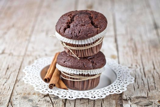 Fresh dark chocolate muffins with cinnamon sticks on white plate on rustic wooden table background.