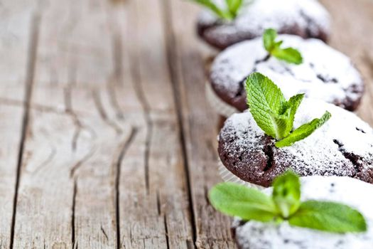 Fresh chocolate dark muffins with sugar powder and mint leaf on rustic wooden table background. With copy space.