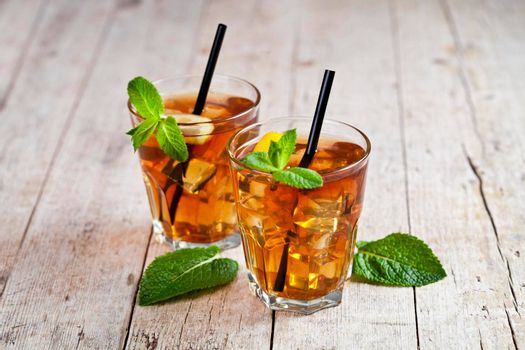 Cold iced tea with lemon, mint leaves and ice cubes in two glasses on rustic wooden table background.