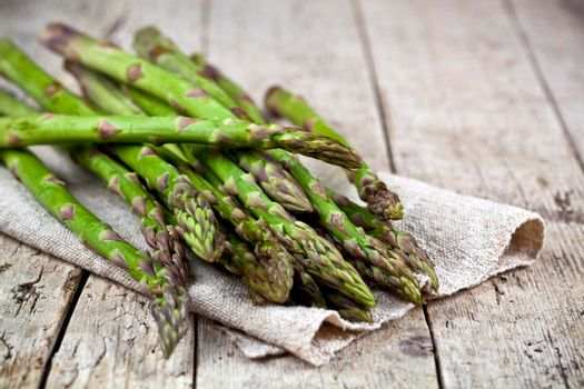 Bunch of fresh raw garden asparagus closeup and linen napkin on rustic wooden table background. Green spring vegetables. Edible sprouts of asparagus. With copy space.