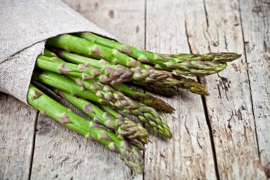 Bunch of fresh raw garden asparagus closeup and linen napkin on rustic wooden table background. Green spring vegetables. Edible sprouts of asparagus. With copy space
