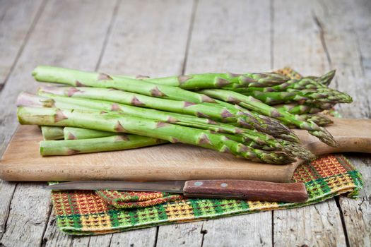 Organic raw garden asparagus and knife closeup on cutting board on rustic wooden table background. Green spring vegetables and cotton napkin. Edible sprouts of asparagus.