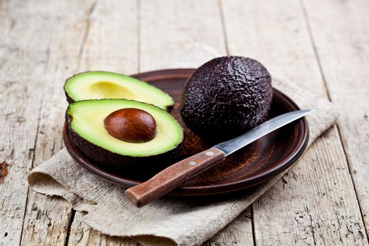 Fresh organic avocado on ceramic plate and knife on  linen napkin on rustic wooden table background. Healthy food concept.