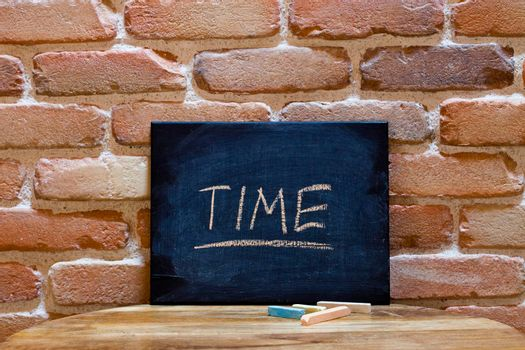 """Black board with the word """"Time"""" drown by hand on wooden table on brick wall background. For business presentation."""