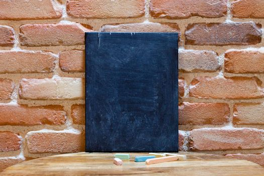 Blank blackboard on wooden table at brick wall, Template mock up for adding your design and text.