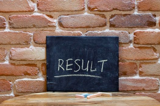 Chalk board with the word RESULT drown by hand on wooden table on brick wall background. For business presentation.