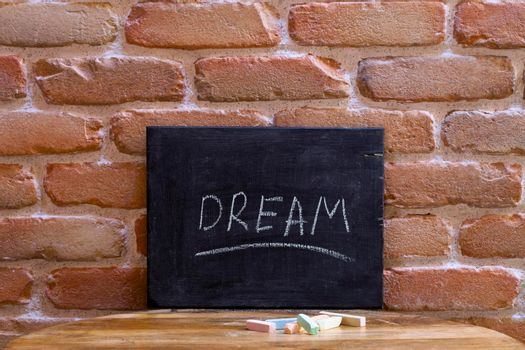 Black board with the word DREAM drown by hand on wooden table on brick wall background. Love concept.